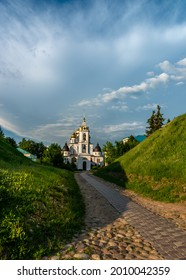 Pathway to the Uspensky Cathedral in Dmitrov near Moscow, Russia, in a park with green lawn and trees in a sunny summer day
