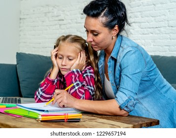 Patience mum with daughter unable to concentrate whilst doing homework sitting on sofa at home in learning difficulties homework parenting and education concept