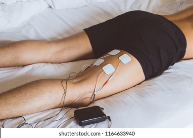 Patient applying electrical stimulation therapy on leg. Electrical tens.