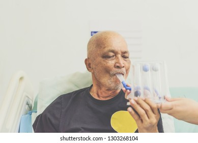 Patient asian elder man 70s use Incentive Spirometer or Triball Tri Flow Meter is medical device to help patients improve the functioning of their lungs on patient bed in ICU. room at hospital.