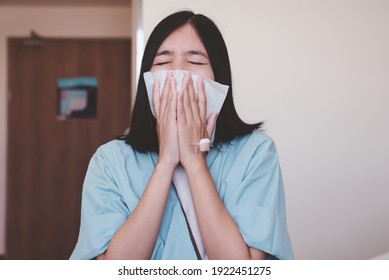 Patient asian women patient sneezing and using tissue paper at hospital