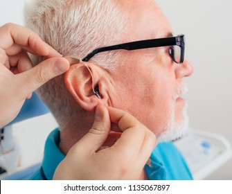 patient is assisted in setting up the hearing aid. Treatment of hearing of elderly people using a hearing aid.