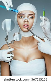 Patient in bandages and many hands holding medical instruments. Nurses holding magnifying glass, syringes, surgical clamp near her face. Plastic Surgery concept