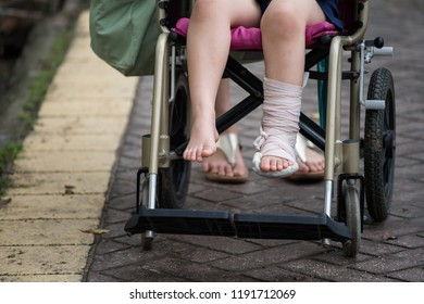 Patient boy sitting on wheelchair to give a walk and refreshment in park. Broken leg by accident wrapped with plaster cast and occlusal splint. Health care and insurance for childern concept.