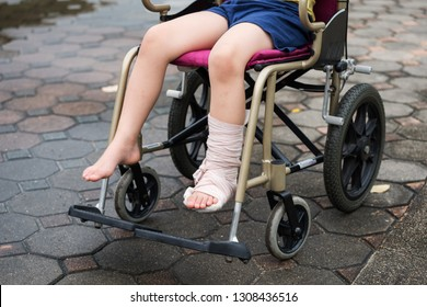 Patient boy sitting on wheelchair to give a walk and refreshment in park. Closeup Broken leg by accident wrapped with plaster cast and occlusal splint. Health kid insurance with copy space for text.
