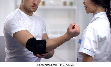 Patient checking elbow pad brace at traumatologist, sports injury, healthcare