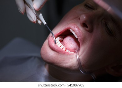 Patient at dentists office, getting teeth examined with hand-held mirror and cleaned of tartar and plaque, preventing periodontal disease. Dental hygiene, painful procedures and prevention concept.