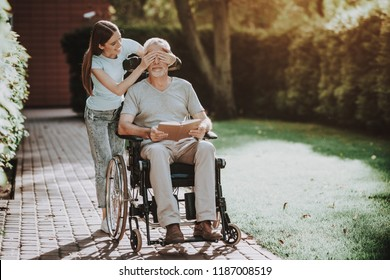 Patient in Family with Young Girl. People and Old Man Together. Physical Loads for Aged. Physiotherapist For Old Man and Family. Professional Walk on Nature with Old Man and Wheelchair. Rehab Aged.