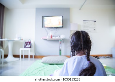 Patient girl watching television in hospital
