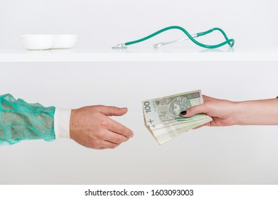 Patient giving a bribe to doctor under table. Giving Polish money for medical services as a bribe