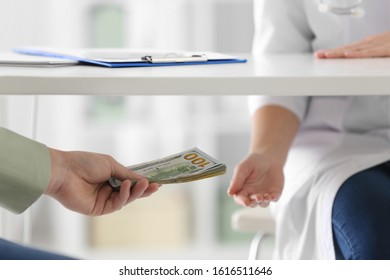 Patient giving bribe to doctor under table in clinic, closeup. Corrupted medicine