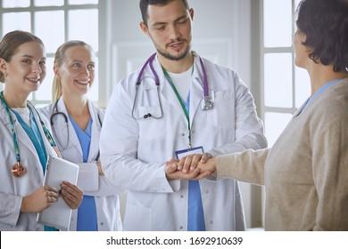 Patient mit einer Gruppe von Ärzten auf dem Hintergrund