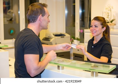 Patient handing an insurance card to doctor's receptionist