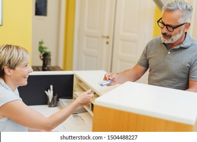 Patient handing over a bank or healthcare card to a medical receptionist behind a counter in a surgery as he checks in for an appointment