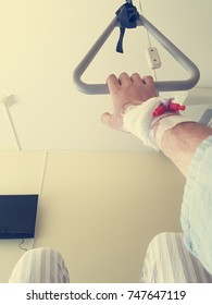 Patient holding a trapeze on a bed - point of view.