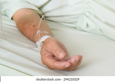A patient in the hospital with saline intravenous, in Asian elderly man hand