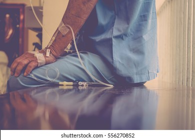 A patient in the hospital with saline intravenous, in Asian elderly man hand , process in vintage style