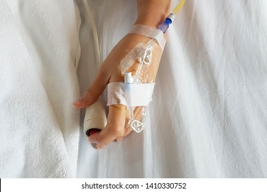 Patient with infusion needle and IV tube for intravenous infusion on hand pressing emergency button on hospital bed; close-up shoot from mobile camera.