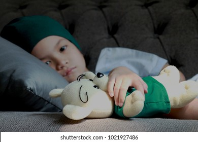 Patient kid lie down on couch or sofa in patient suit with her doll.Girl cover her head with  blue hat or headscarf.Kid look sad,tired and sick.Concept of   childhood cancer awareness.Selective focus.