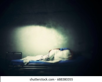 Patient lay down in the bed at hospital. Sick and coma. Blur picture and dark tone.
