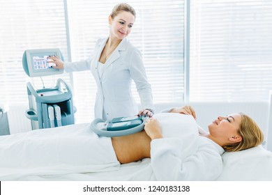 patient lies on medical table undergoing cryolipolys procedure to fat reduction. Beauty vibrant massage therapy combined with crio effect gives excellent results. Body weight loss, Anti cellulite.