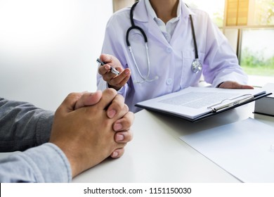 patient listening intently to a male doctor explaining patient symptoms or asking a question as they discuss paperwork together in a consultation.