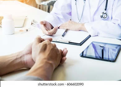 patient listening intently to a male doctor explaining patient symptoms or asking a question as they discuss paperwork together in a consultation