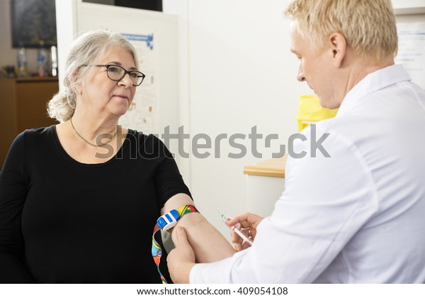 Patient Looking At Male Doctor Collecting Blood In Syringe