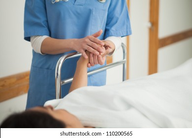 Patient lying on a medical bed holding the hand of a nurse in hospital corridor