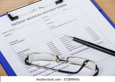 Patient medical history form on clipboard with pen and eyeglasses laying on a desk
