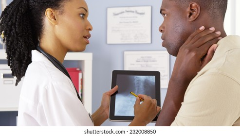 Patient with neck pain talking to female doctor about x ray on tablet