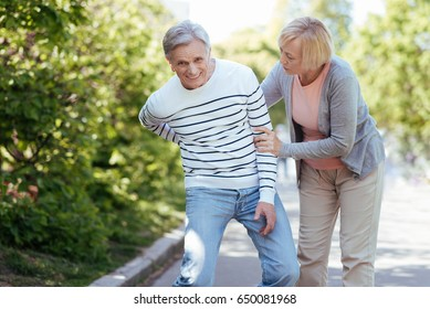 Patient old woman taking care of ill man outdoors