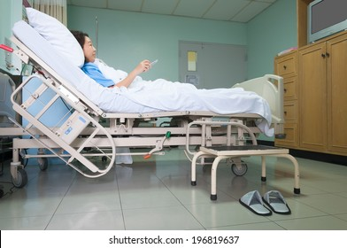 Patient on gurney and watching TV in hospital room.