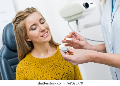 patient and optician with contact lens in clinic