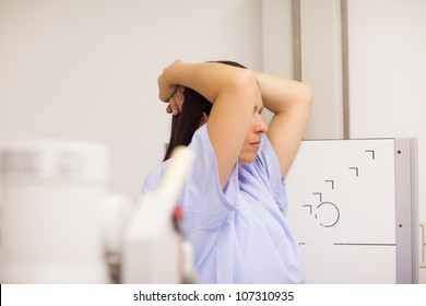 Patient placing her arms on her head while standing in front of a machine in an examination room