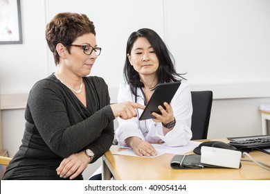 Patient Pointing At Digital Tablet Held By Doctor