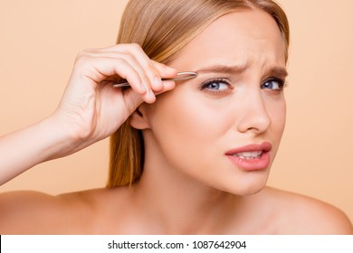 Patient, pretty, nude, natural model looking at camera plucking eyebrows with tweezers, having pain, isolated on beige background, perfection, wellness, wellbeing concept