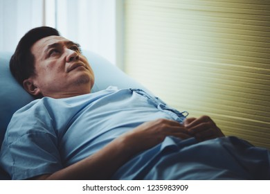 Patient senior man lying on bed resting tired looking sad