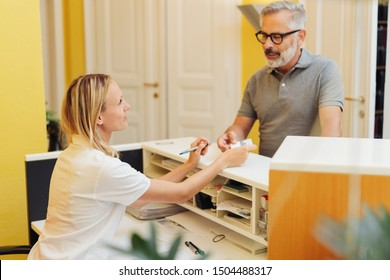 Patient settling up with a receptionist in a medical surgery after an examination by a doctor or dentist