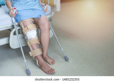 Patient sit on bed in hospital ware knee brace support after do posterior cruciate ligament surgery ,Bandage on knee of asian woman on crutches.healthcare and medical concept.