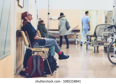 Patient sitting in hospital ward hallway waiting room with iv. Woman with intravenous therapy in her hand is waiting in the clinic corridor with blurred medical personnel in background.