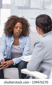 Patient sitting on sofa and talking to therapist during therapy