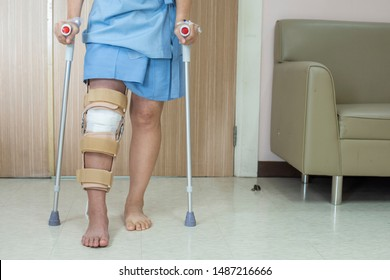 Patient standing on crutch in hospital ward ware knee brace support after do posterior cruciate ligament surgery ,Bandage on knee of asian woman on crutches.healthcare and medical concept.