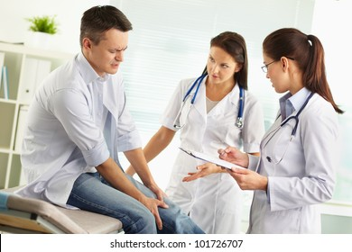 Patient suffering from pain in the leg being examined by a female doctor and her assistant