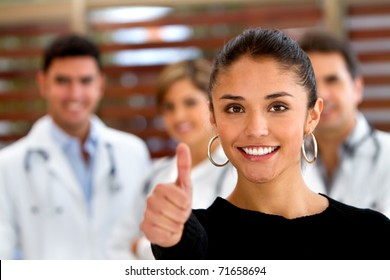 Patient with thumbs up and a group of doctors at the background