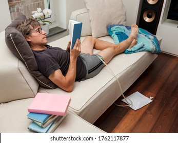 Patient with urethral catheter inserted into the penis, reads a book lying on the sofa at home.