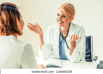 Patient visit doctor at hospital. The happy female doctor is talking and smiling to the patient. Concept of healthcare and doctor service.