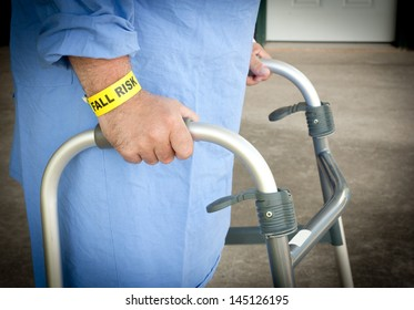 A patient walking with a walker wearing a fall risk bracelet and blue gown