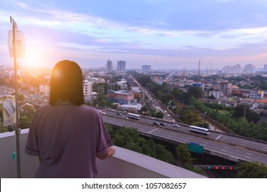 Patient wearing violet cloth need to go back home. Woman sickness standing on balcony of hospital room was homesick and looking at the sky in the direction of her home with sunset or sunrise