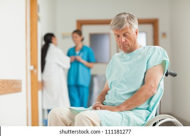 Patient in a wheelchair looking down in hospital ward